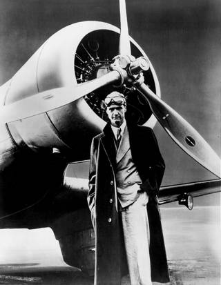Howard Hughes poses in front of the his record setting Northrop Gamma Monoplane in this 1930s photo. Hughes broke his first aviation record in the Gamma when he made the west-east American transcontinental run in 9 hours, 26 minutes, and 10 seconds.