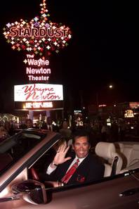Entertainer Wayne Newton waves beneath the sign at the Stardust hotel-casino after turning on its switch in Las Vegas on Thursday, Jan. 20, 2000. The hotel was demolished in March 2007.