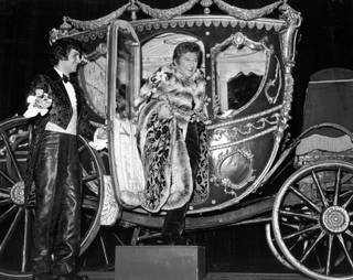 Liberace arrives at one of his shows at the Las Vegas Hilton, in an extravagant horse-drawn carriage. The singer's lavish costumes and stage props were funded by his $125,000 weekly salary.