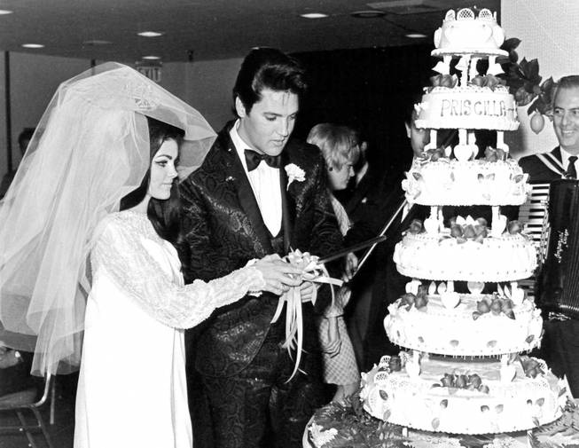 Elvis and Priscilla Presley cut their wedding cake after exchanging vows in the Aladdin Hotel-Casino on May 1, 1967.