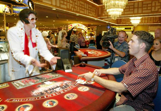 An Elvis Presley impersonating dealer flips a blackjack to Martin Paquin of Montreal, Quebec, during the unveiling of the Legends Pit at Imperial Palace in September 2003. The lineup of celebrity impersonating blackjack dealers, or dealertainers, includes Elvis, Liberace, Buddy Holly, The Blues Brothers, Madonna, Patsy Cline, Marilyn Monroe, Barbra Streisand, Rod Stewart, Elton John and Ray Charles.