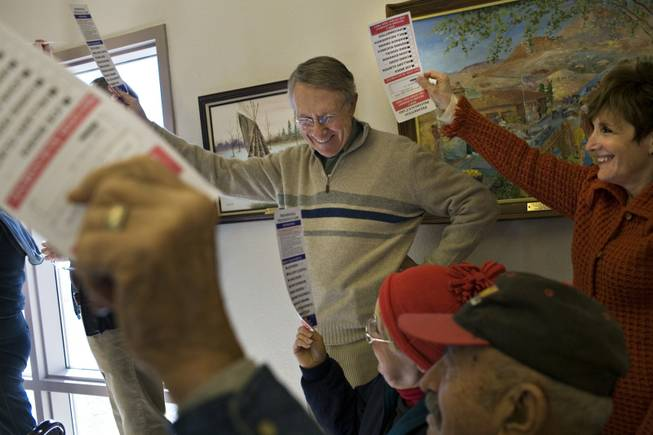 Sen. Harry Reid and his wife, Landra Gould, raise their presidential preference cards to be counted at their home precinct in Searchlight during the Jan. 19 Democratic presidential caucus. Reid hasn't said whom he is backing in his party's nominating race, and his new book offers few clues, praising both Sen. Hillary Clinton and Sen. Barack Obama.
