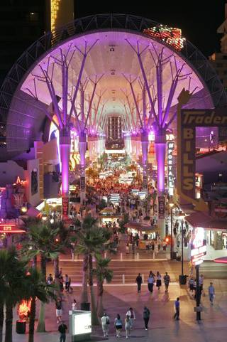 The Fremont Street Experience glows under its canopy as thousands of tourists patronize the businesses and casinos located on the historic street.