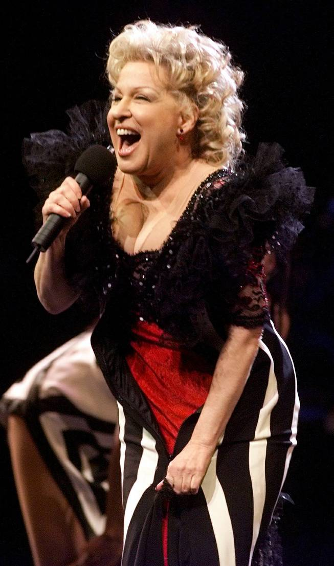 Bette Midler unzips her dress in the middle of a song to reveal another outfit underneath during a performance at the Mandalay Bay Events Center on New Year's Eve Friday, December 31, 1999.