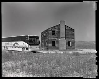 The tour bus passes a two-story building used in the Apple II tests during the monthly public tour of the Nevada Test Site