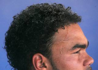 Beads of water from an overhead mister form on Las Vegas 51's pitcher Ramon Troncoso's hair and forehead as he sits in the dugout during a rare day game at Cashman Field.