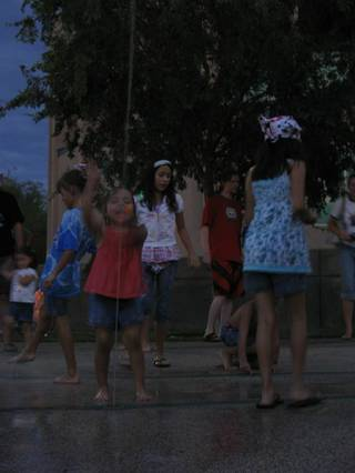 A young girl plays in the water at the Henderson Events Plaza and Convention Center before the annual Fourth of July fireworks.