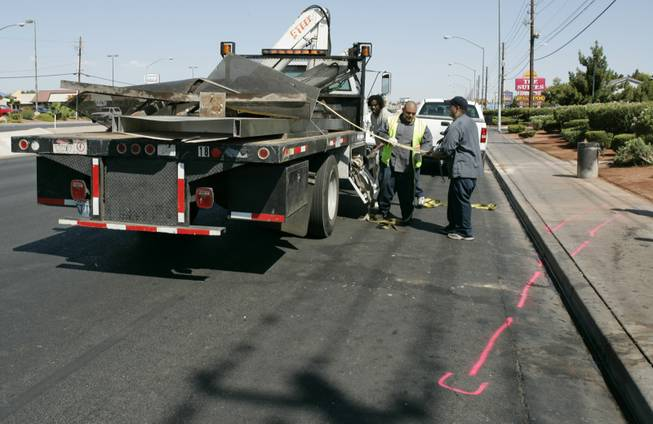 A clean-up crew loads the remains of a bus stop after a crash on Boulder Highway, just north of Flamingo Road, that killed one person who was waiting for a bus in July 2008. Another person who was at the bus stop and the driver of a sport utility vehicle were also hospitalized.