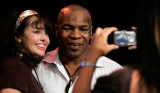 Mike Tyson poses for a photo with fan Michele Mosey before the Lynel Burton and Chris Finley welterweight boxing match at the Las Vegas Hilton.