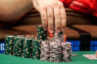 Joe Bishop plays with his chips during one of the two final tables of the WSOP World Championship No Limit Texas Hold 'em event.