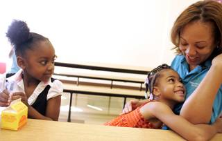 Nilah Pierce, from left, watches as Avianna Chappel hugs project director LaShelle Whitmore during the Rainbow Dreams Academy charter school's summer enrichment program in Las Vegas Monday, July 20, 2009.