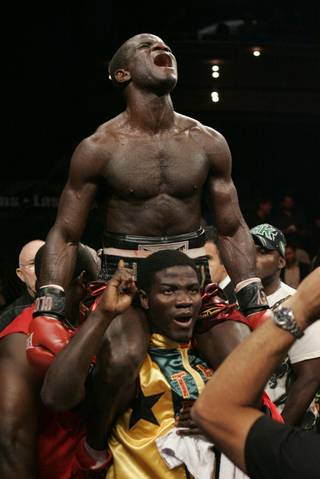 Joshua Clottey celebrates his IBF welterweight title victory over Zab Judah Saturday night at the Palms Casino in Las Vegas. Clottey won by unanimous decision in the ninth round when Judah could no longer fight because of a large cut over his right eye.