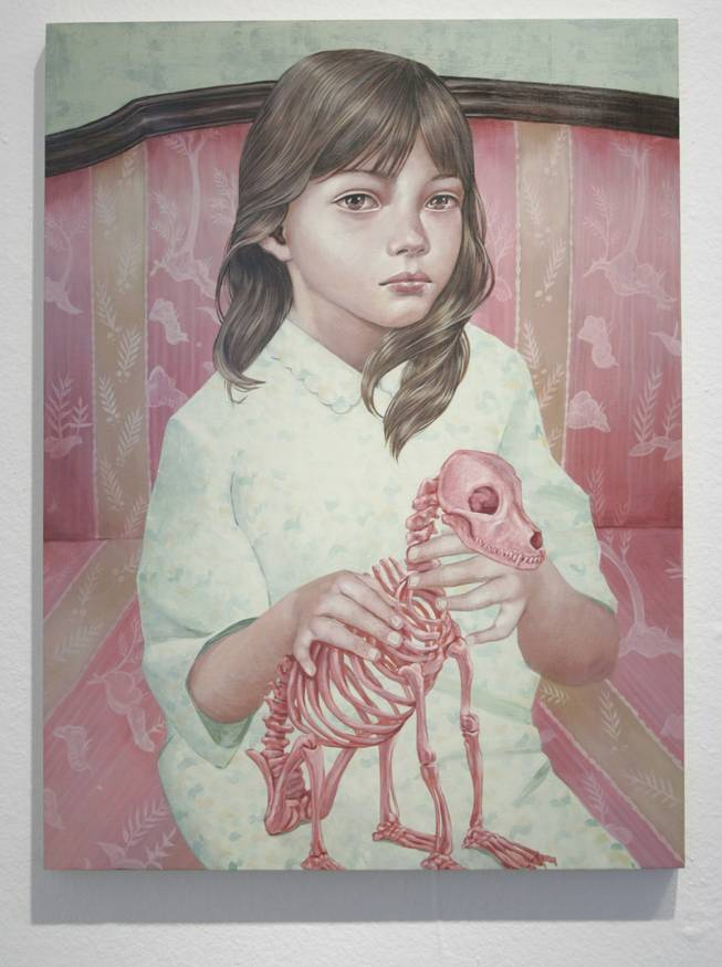 Something is off kilter: The young girl in a flannel nightie sitting on a Victorian settee holding the pink skeleton of a pet dog creates a perfectly ambiguous scene.