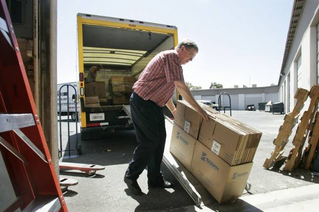 Dean Warner loads boxes into his warehouse at Moving Box Rentals that were left over from Steve Saltzman closing his business for a move to Los Angeles last week.