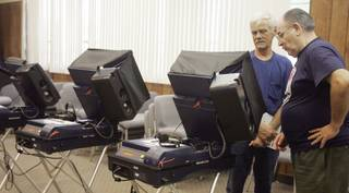 With the help of volunteer, Manny Escobedo, right, Russell Murray, left, takes advantage of early voting for the primary election at City Hall in Boulder City on Aug. 5.