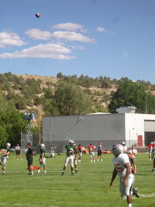 Jason Davis, in white, runs down a fade pass from Omar Clayton Sunday afternoon during UNLV football practice in Ely. The Rebels are up in the mountains until Aug. 19.
