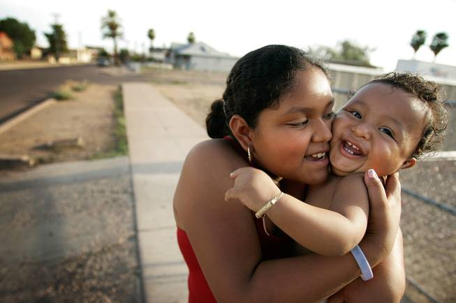 """He's always smiling at people. Even with strangers,"" said big sister Gabriella Ramirez, 10, when I commented that her little brother, Jovany, was probably the most smiley and cute 1-year-old I had ever seen. Jovany loved to smile, and then when I got too close, loved to bat at my camera lens. I met them while videographer Matt Toplikar and I were cruising through one of the Hispanic neighborhoods in town, talking to people about the election. <em> - Leila Navidi</em>."