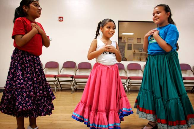 After a breathless round of rehearsing ballet folklorico, traditional Mexican folk dance, at the Viva Performing Arts Center in Tucson, 8-year-old friends, from left, Kiana Medrana, Sofia Espinoza and Gabriella Carrillo feel their chests for their quickened heart beats, giggling at how fast their hearts are beating after a good round of dancing. -- Leila Navidi