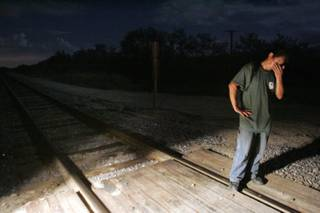 An alleged illegal immigrant stands by a railroad track after being spotted by the Minuteman Civil Defense Corps of Arizona on a private ranch near Amado, Ariz. The rancher asked the Minuteman Corps to set up a muster, or a border watch operation, to look for illegal immigrants using his ranch to avoid a Border Patrol checkpoint on Interstate 19, a road that comes south toward Tucson, Ariz., from Nogales, Sonora, Mexico. The rancher suspected that the immigrants were dropped off south of the border checkpoint, making their way on foot through his ranch, to be picked up by car on I-19 at a designated area north of the checkpoint. This man was the last of 13 people spotted by the Minuteman Corps, and then picked up by the Border Patrol that night.