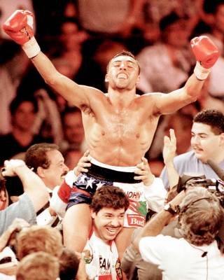 Oscar De La Hoya celebrates his win over Julio Cesar Chavez on the shoulders of his trainer at Caesars Palace in 1996.