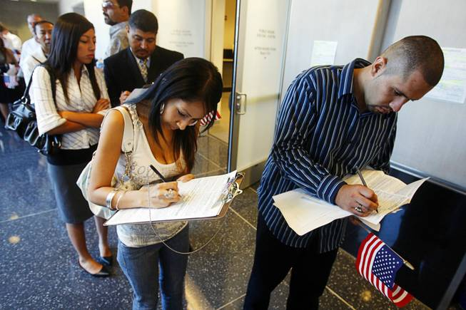 New U.S. citizens Jenette Chavez, 18, left, and Josue Cano, 20, fill out forms as they register to vote at the George Federal Building in Las Vegas on Aug. 22, 2008.