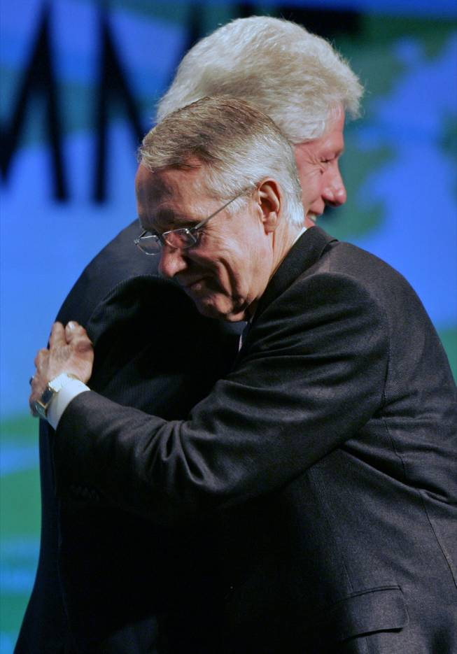 Senate Majority Leader Harry Reid, foreground, gives a hug to former President Bill Clinton during the opening session of the National Clean Energy Summit on Monday at the Cox Pavilion.