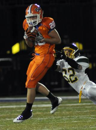 Bishop Gorman safety No. 20 Evan Zeger leaps to intercept a pass intended for Service Cougars wide receiver No. 32 Neil Miyaoka during the first half of the Gaels' home opener on Friday.