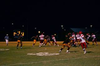 Players spring into action as the ball comes into play during Friday night's football game at Del Sol.