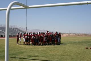 The Desert Oasis football team gathers on its new football field Thursday for its last practice before Friday's opening game.