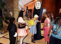 Maganda Antonio, 11, hugs Sherri Kohli, 15, dressed as an 8-foot character from a Japanese animated movie, during the annual Anime Vegas convention Sunday at the Renaissance Hotel. Many who attended the dress-up party made their own costumes.