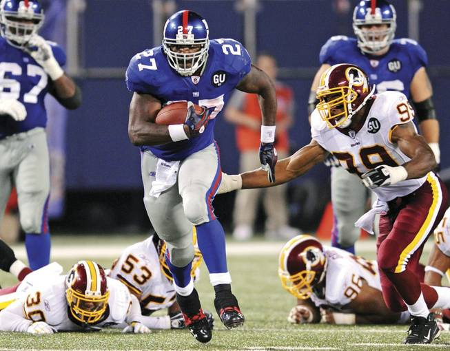 New York Giants running back Brandon Jacobs is in the midst of a 16-yard run as the Washington Redskins' Andre Carter, right, closes in during New York's 16-7 win Thursday at Giants Stadium in East Rutherford, N.J. In Nevada casinos football is king -- last year college and NFL bets totaled a record $1.17 billion, up from $1.13 billion in 2006.