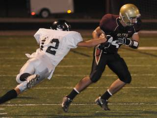 Crusaders wide receiver Don Pearson protects the ball from Spring Creek tackler Marty Shanks during a game at Faith Lutheran High School on Friday night.