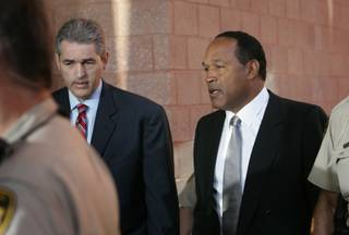 O.J. Simpson, right, talks with attorney Gabrial Grasso as they arrive at the Clark County Regional Justice Center on the first day of jury selection Monday. Simpson is appearing in court on charges that include burglary, robbery and assault following an incident at Palace Station Hotel & Casino in September 2007.