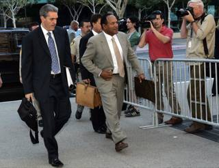 O.J. Simpson arrives Monday for the first day of his trial at the Clark County Regional Justice Center. Attorney Gabriel Grasso is at left.