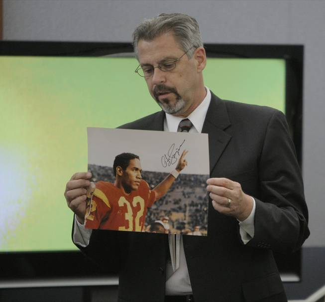 Bruce Fromong displays a signed photo entered into evidence  during O.J. Simpson's trial in Las Vegas, Tuesday, Sept. 16, 2008.