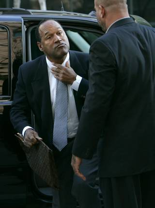O.J. Simpson adjusts his tie as he arrives at the Clark County Regional Justice Center in Las Vegas, Nev., Wednesday, Sept. 17, 2008. Simpson faces charges that  include burglary, robbery and assault following an alleged robbery at the Palace Station Hotel & Casino in Sept., 2007.
