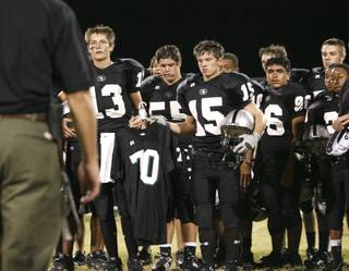 Chaisson Prescott (13) and Tyler Leet (15) hold the jersey of Christopher Privett, a Palo Verde freshman who was shot and killed while walking home in February. The school retired Privett's jersey during a halftime ceremony Thursday.