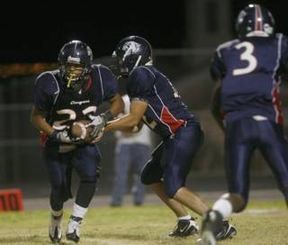 Coronado quarterback Michael Scott (12) hands a pass to Marcus Garcia (22) during Friday's home against Basic.