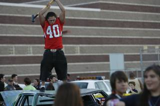 At the tailgate party before Coronado High School's homecoming game against rival Green Valley, senior Steve Salgado hits a car painted with anti-Gator slogans with a sledgehammer.