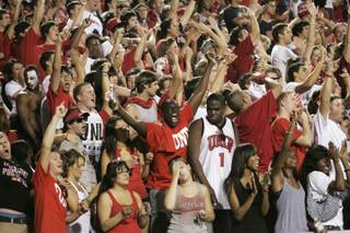 UNLV fans cheer as their team takes the field against UNR at Sam Boyd Stadium.
