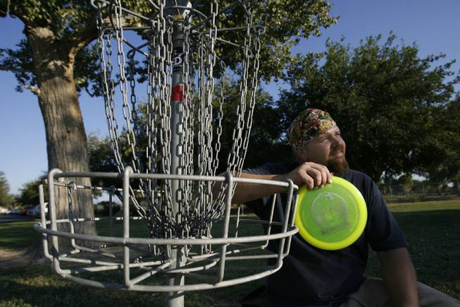 Disc golfer Robert Schuler, a member of the Professional Disc Golf Association, poses next to a disc golf basket Wednesday at Sunset Park. He's worried that upcoming renovations at the park will affect the course.