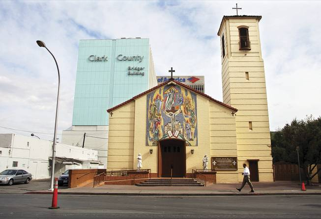 Saint Joan of Arc Roman Catholic Church on Casino Center Boulevard in downtown Las Vegas is dwarfed by commercial buildings.
