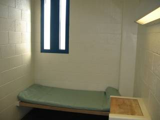 The bed and desk in the jail cell.