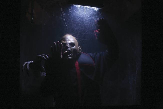 A zombie beats on the glass towards haunted house goers at Fright Dome in Circus Circus.