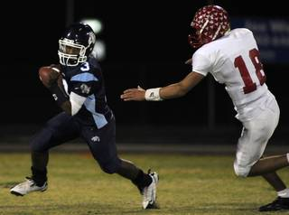Bulldogs quarterback Chris Henderson (3) looks to evade Arbor View's Austin Anderson (18) during Friday's game at Centennial High.