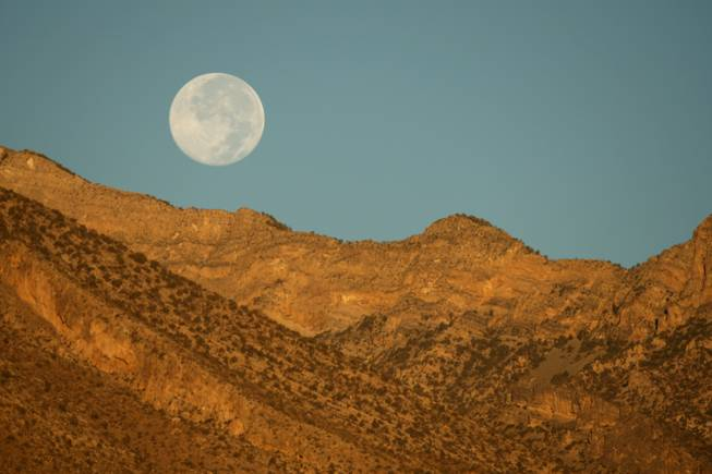 A full moon sets over the mountains at sunrise Wednesday, Oct. 15, 2008. The view is  from Summerlin Parkway and the I-215 Beltway.
