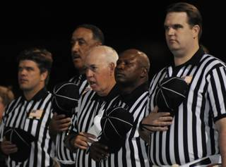 Football officials remove their caps during the national anthem Friday during pre-game ceremonies at Arbor View High School on Friday.