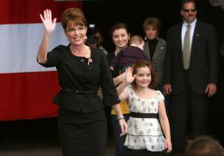 Republican vice presidential nominee Alaska Governor Sarah Palin, left, arrives for a rally with daughters Piper, right, 7, and Willow, center, 13, and son Trig (held by Willow) in Henderson, Nev. Oct. 21, 2008.