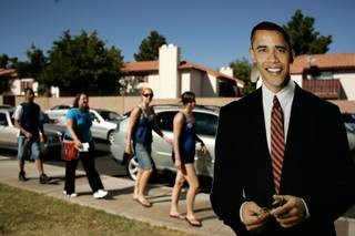 Supporters walk by a cardboard cutout of Sen. Barack Obama before a rally with the Democratic presidential candidate at Bonanza High School on Saturday.