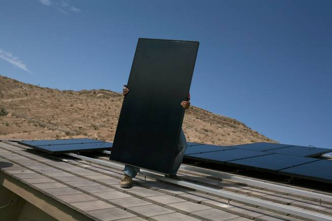 Electrician Frank Cudia of Bombard Electric carries a solar panel for installation this month on the roof of a home in Las Vegas. Developers of large solar arrays say Nevada doesn't offer kinds of the incentives or workforce other states do.